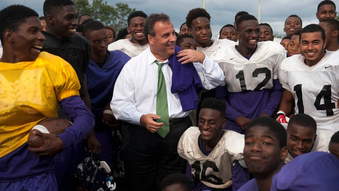 Gov. Chris Christie poses for  a team photo  with  Camden High School's football  players during practice at their field in Camden on Wednesday. The governor also spoke Elijah Perry Park and toured the KIPP-Cooper Norcross Renaissance School during his visit to the city, where he praised the crime-fighting efforts of the Camden County Police Department.