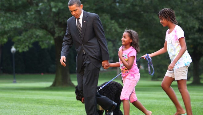 President Obama is welcomed home from daughters Sasha and  Malia (and dog Bo) on the south lawn of the White House September 15, 2009.
