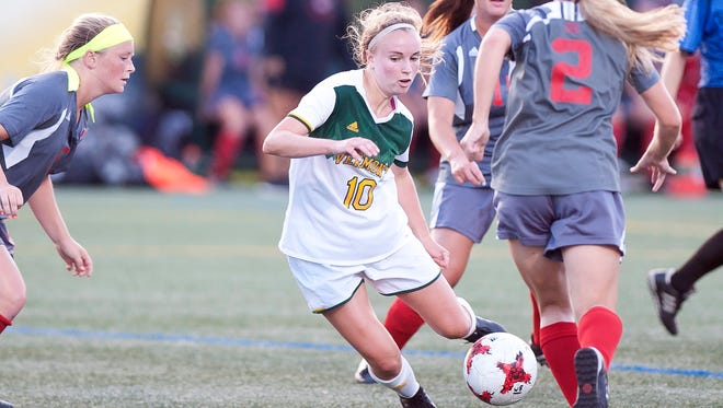 University of Vermont forward Ella Bankert, center, dribbles through the Sacred Heart defense during Friday night's women's soccer game at Virtue Field.