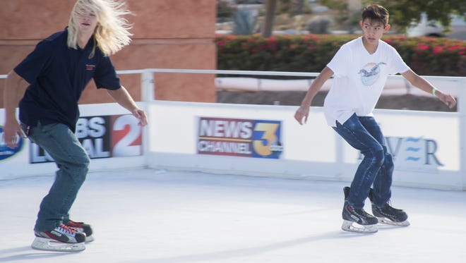 From left, Blake Aiken and Mark Canseco skate backward at the Renova Ice Rink at The River in Rancho Mirage on December 9, 2017.