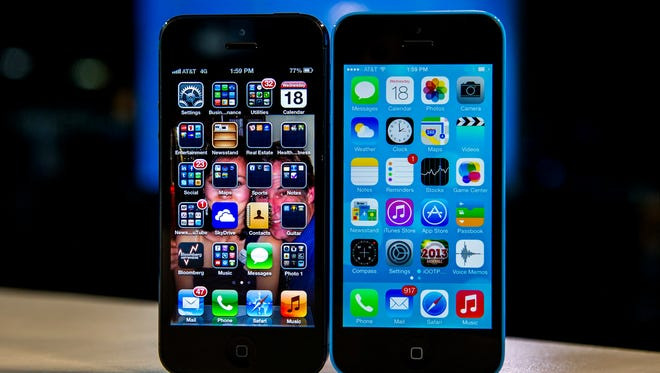 The home screen of an iPhone 5 operating iOS 6, left, and an iPhone 5C operating iOS 7.