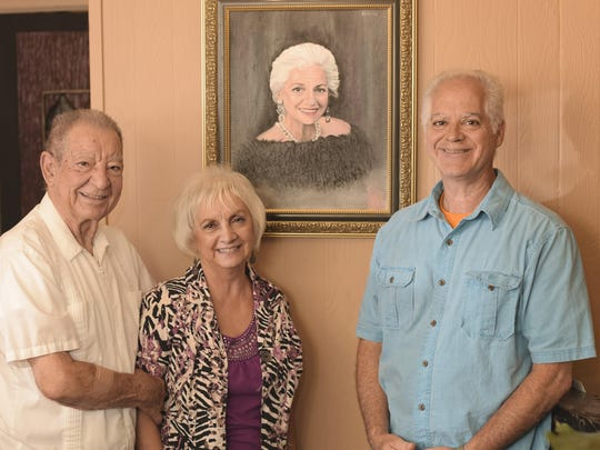 Buzz Baudo with his daughter, Sharon Smith and his son, Jack Baudo, stand beneath the portrait of Helen Baudo, restaurant founder in the entrance to Baudo's Restaurant.