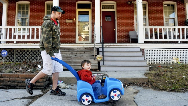 Dave Robertson walks home with his son Danny, 2, on Pennsylvania Avenue in York's Avenues neighborhood. Robertson, a stay-at-home father, said he and his family will probably leave the area for a more suburban or rural setting once Danny is of school-age. The neighborhood, often described as quiet, features a wide variety of residential architecture that reflects the area's growth, from Victorian houses to American Craftsman-style homes to bungalows to ranch houses.