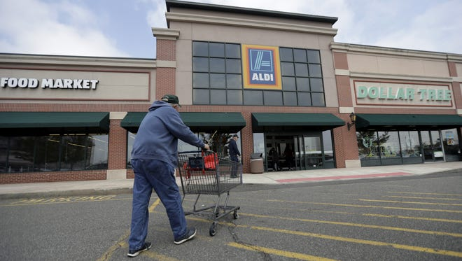 A customer approaches the entrance of an Aldi food market, in East Rutherford, N.J., in this May 31, 2017, photo. The discount grocery retailer is opening a regional office and distribution center in Goodyear, and Arizona stores are expected to follow.