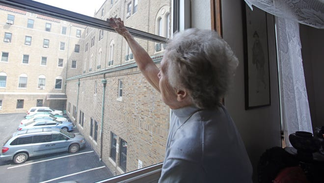 """Jeanne Houlihan tries to open the window at Maryknoll Sisters in Ossining on July 7, 2015. The Maryknoll Sisters in Ossining are trying to raise money to replace 403 windows at the """"Motherhouse,"""" which is home to elderly retired nuns."""