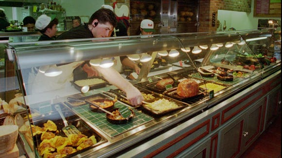 An employee stirs food on a restaurant buffet table.