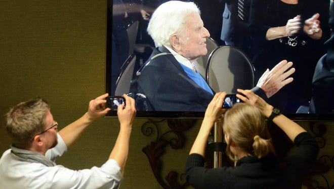 Journalists photograph a television monitor in the media room at the Grove Park Inn as Billy Graham arrives for a celebration of his 95th birthday in Asheville, N.C., on Nov. 7, 2013.