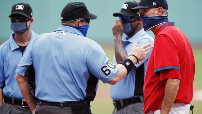 """Boston Red Sox manager Ron Roenicke (right) talks with home plate umpire Marty Foster  before a baseball game against the Baltimore Orioles on July 25, 2020, in Boston. Roenicke says his club has been """"really good so far"""" when it comes to handling the coronavirus. His team is set for its first road trip of the season on Wednesday."""