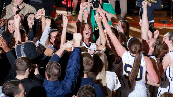 DeWitt players and fans celebrate their 65-37 win over Grand Rapids Forest Hills Central in their MHSAA Quarterfinal game Tuesday, March 17, 2015, at Charlotte High School.