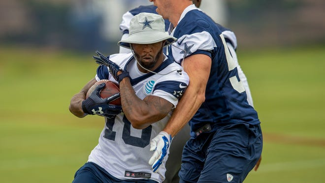 FILE - In this July 26, 2018, file photo, Dallas Cowboys running back Tavon Austin, left, runs by teammate linebacker Sean Lee during NFL football training camp in Oxnard, Calif. Austin never really had a fresh start with a new coach in Los Angeles because of a wrist injury that plagued him and a hamstring that popped on him before the last of five disappointing seasons with the Rams. The eighth overall pick in the 2013 draft believes the opportunity has arrived through a trade to the Cowboys and the health that Austin hoped would come with it. (AP Photo/Gus Ruelas, File)