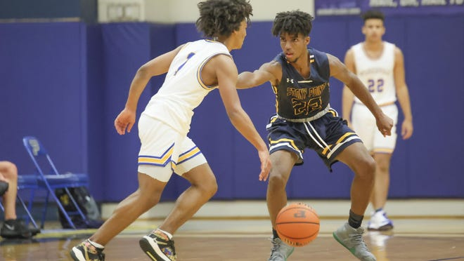 Stony Point's Lamont Norton plays close defense against Pflugerville in the first half of a nondistrict game Tuesday at Pflugerville High School. Stony Point pulled away for a 69-59 win.