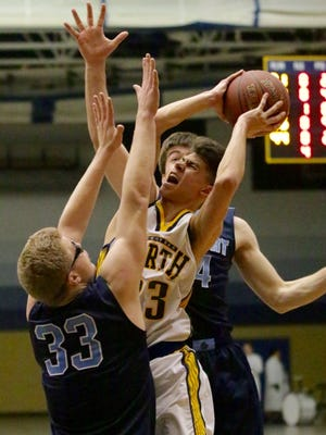 Sheboygan North's Zach Hasenstein goes up for a shot between a pair of Bay Port defenders on Tuesday night.