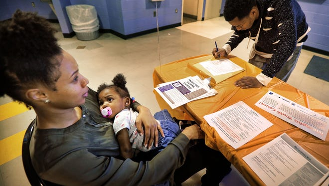 Volunteer Alyncia Clark (left) keeps an eye on  London Campbell, 1, while Ryan Mobley fills out a survey form  during a  Community Alliance for the Homeless Memphis Youth Count at the North Frayser Community Center.