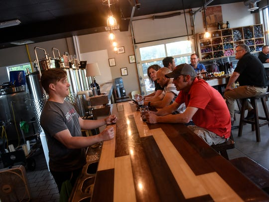 Bad Habit Brewing Company co-owner Eric Geier talks with customers Thursday, May 24,  at the St. Joseph taproom.
