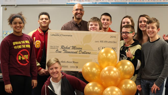 Rahul Menon, math teacher at McCutcheon High School, was one of five educators selected for the Golden Apple awards. He holds a check presented to him earlier this week.