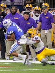 LSU linebacker Jonathan Rucker (51) tackles BYU running back Trey Dye (4) in the open field as LSU head coach Ed Orgeron, center, watches the play in the second half in New Orleans, Saturday, Sept. 2, 2017.