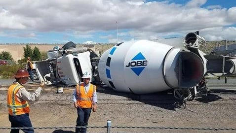 A concrete mixing truck crashed on Interstate 25 Friday morning after a tire blew causing the driver to lose control.