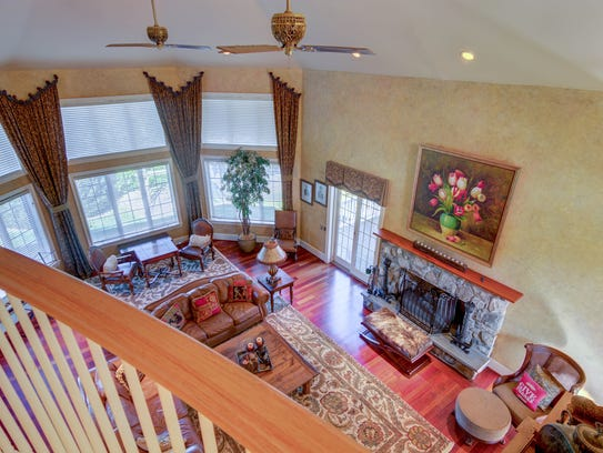 The spacious, two-story family room is sunlit by floor-to-ceiling