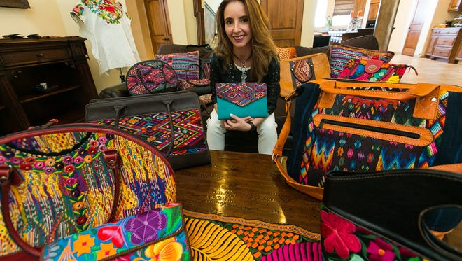 Maria Mercedes Colato, owner of Roots Leather Company, is surrounded by a variety of Guatemalan inspired handbags and accessories on Monday, March 14, 2016, at her Las Cruces home.