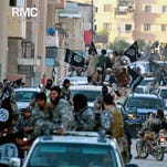 In this undated file image posted on June 30, 2014, by the Raqqa Media Center of the Islamic State group, a Syrian opposition group, which has been verified and is consistent with other AP reporting, fighters from the Islamic State group parade in Raqqa, northern Syria.
