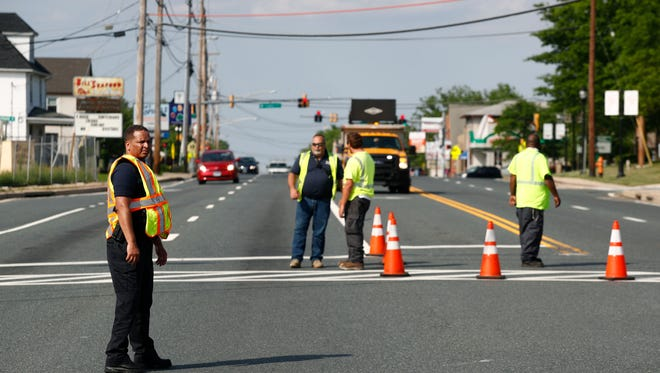 Officials guard a roadblock near a scene where a Baltimore County police officer died, while investigating a suspicious vehicle, Monday, May 21, 2018, in Perry Hall, Md. Heavily armed police swarmed into the leafy suburb, searching for at least one armed suspect.