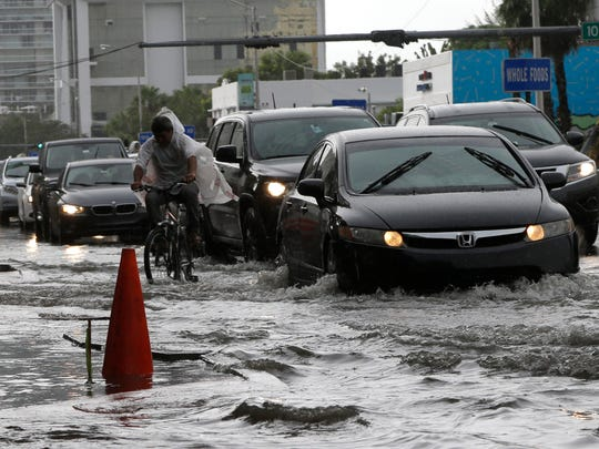 A cyclist and vehicles negotiate heavily flooded streets as rain falls, Tuesday, Sept. 23, 2014, in Miami Beach, Fla. Certain neighborhoods regularly experience flooding during heavy rains and extreme high tides. National and regional climate change risk assessments have used the flooding to illustrate the Miami area's vulnerability to rising sea levels.