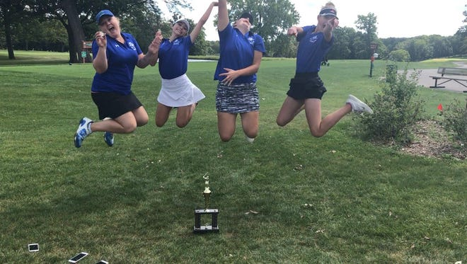 Oak Creek senior Alexis Hecker, junior Lily Gough, senior Ashley Arndt and freshman Ellie Behring jump for joy after the Knights recorded their first event victory in program history.