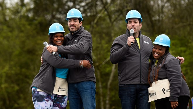 Amanda Osborne hugs Property Brothers' Jonathan Scott, left, as they address the media with Drew Scott and Ashlee Walker Pride before raising the walls to their new homes with volunteers from Habitat for Humanity in Nashville, Tenn., Monday, April 2, 2018.