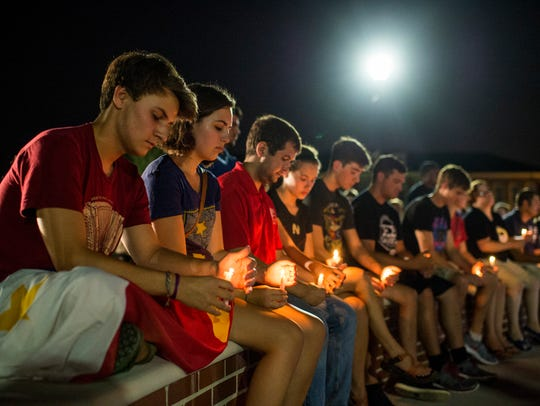 Students gather to mourn during a candlelight vigil