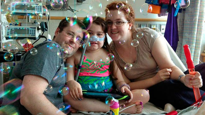 Sarah Murnaghan celebrates the 100th day of her stay in Children's Hospital of Philadelphia on May 30. She poses with her father, Fran, and mother, Janet.