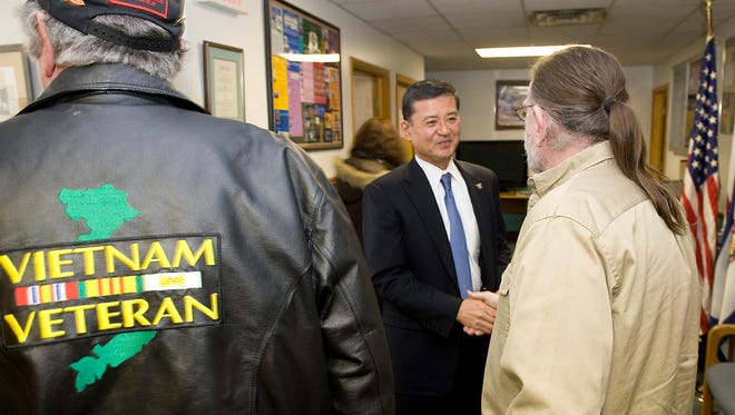 Veterans at the Charleston Vet Center in West Virginia greet Veterans Affairs Secretary Eric Shinseki, center, in 2010.  Shinseki has said he's making it a top priority to tackle the veterans disability claims backlog, but the government shutdown has tabled any overtime for claims processors, who remain on the job.