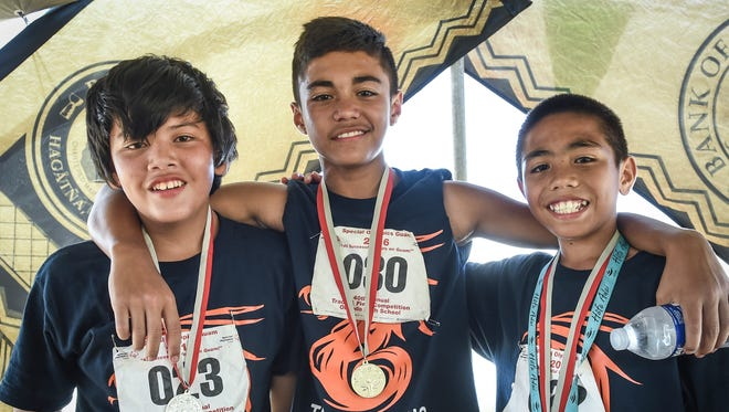 From left, Erik Dela Cruz, Donovan Santos, and Ivan Blas, all from Astumbo Middle School, win medals in the 200 meter dash the 40th annual Special Olympics Guam Track and Field Event at Okkodo High School on March 19.