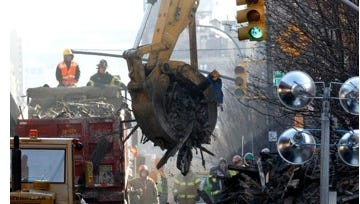 Crews remove rubble onto a dump truck Thursday, March 13, 2014, as debris is cleared from the site where two buildings were leveled a day earlier during an explosion,  in New York City. The explosion Wednesday, March 12, 2014, on Park Avenue at East 116th Street in Manhattan's East Harlem killed at least eight and injured more than 60 people.