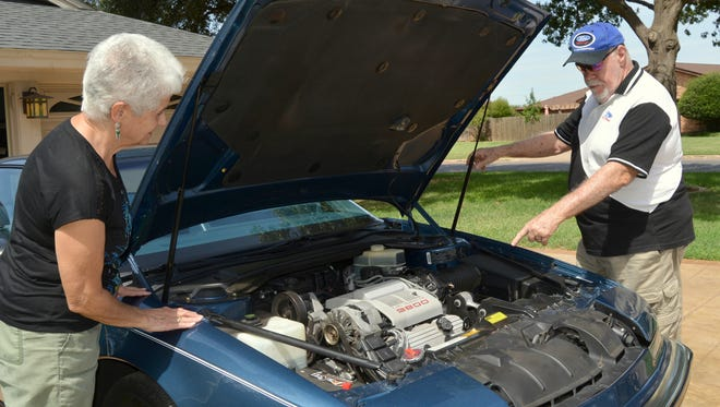 VERNON – Molly Baldwin listens as her husband Reg explains that the engine under the hood of his 1989 Buick Reatta is all original equipment. The vehicle has only been driven about 30,000 miles.