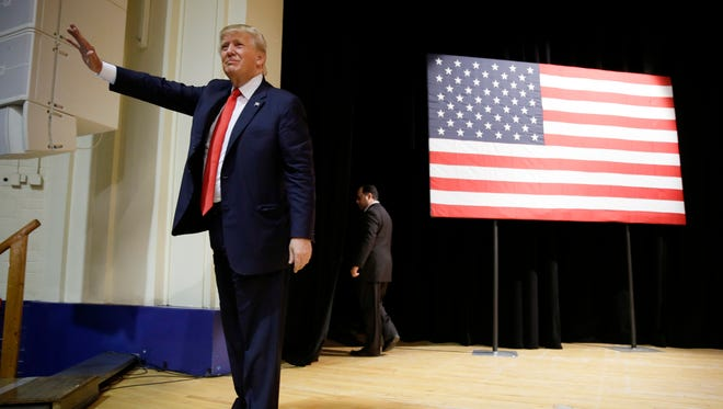 Republican presidential candidate Donald Trump waves to supporters as he leaves a campaign stop at the Burlington Memorial Auditorium, Wednesday, Oct. 21, 2015, in Burlington, Iowa.