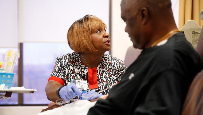 Texas Health Presbyterian Hospital of Dallas Infusion Center oncology nurse Donna Tusan gives Robert Smith a dose of medication to boost his immune system at their center in Arlington, Texas.