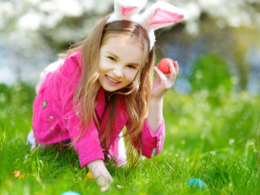 Adorable little girl hunting for easter egg in blooming spring garden
