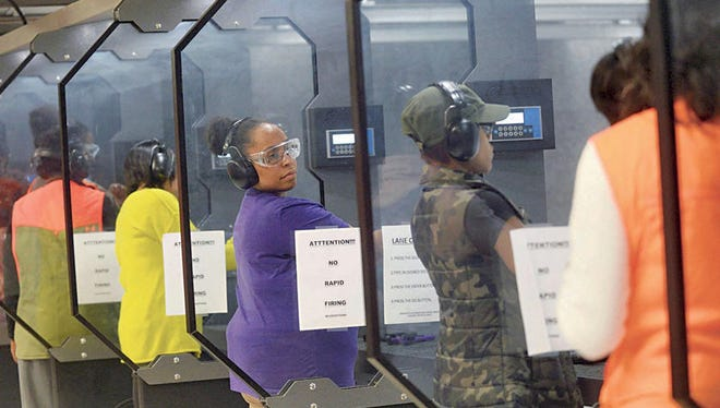 April Hayes, center, of Farmington gets ready to practice at the Action Impact Firearms & Training Center in Eastpointe.