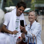 Roger Federer poses for a photograph following a practice session ahead of the 2015 Wimbledon Championships at the All England Tennis Club.