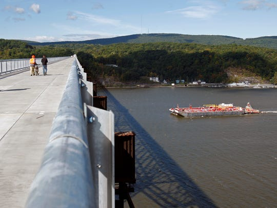 A barge cruises under the Walkway Over the Hudson in