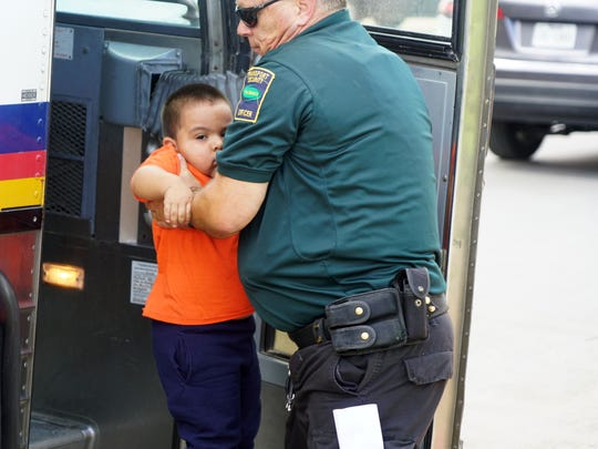 A migrant boy released from federal custody gets help down from a bus by a private security guard in McAllen, Texas, on June 22, 2018.