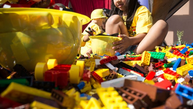 Isabella Munoz (kindergarten, Grace Community Christian School) plays with Lego bricks that were dumped in the parking lot during the groundbreaking ceremony for the $12 million Legoland Discovery Center being built at Arizona Mills, 5000 S. Arizona Mills Circle, Tempe.