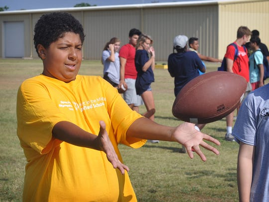 Braeden Ball of Barwise Middle School catches the football while competing in the Special Olympics Unified Sports Day at Rider High School Thursday morning. Nearly 200 athletes from nine area schools participated in five events.