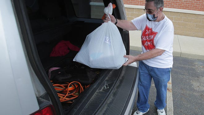 Massillon Salvation Army volunteer Glen Buttacavoli puts a bag of school supplies into a vehicle for a family at the Massillon Salvation Army's annual back-to-school giveaway. The Salvation Army had to change how it typically distributes its supplies this year due to the coronavirus pandemic.