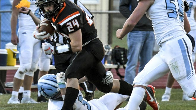 Holcomb High School's Levi Knoll (24) runs over Clearwater's Aiden Brockman on a carry Friday at Holcomb in a Week 9 playoff game. The Longhorns season came to a close with a 31-15 loss.