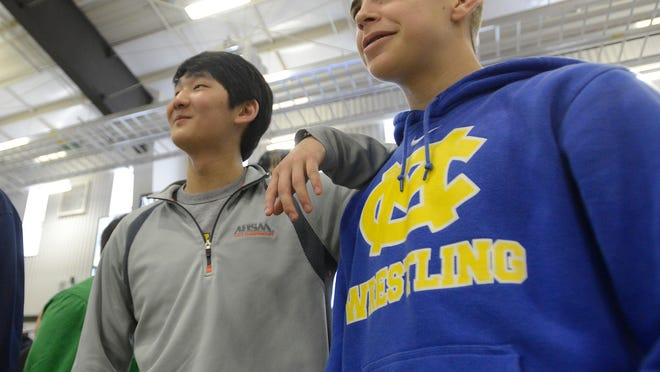 Catholic's Zach Van Alst, right, hangs out with Stephen Kwan, who wrestled last year for St. James, at the wrestling sectional meet at Cramton Bowl on Saturday.