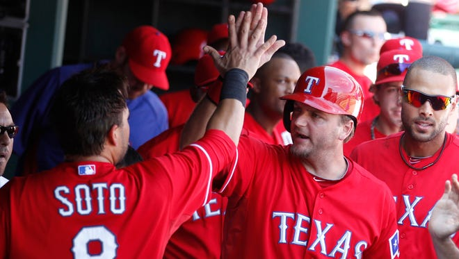 Rangers designated hitter A.J. Pierzynski, right, high fives Geovany Soto after they scored runs in the fifth inning Sunday.