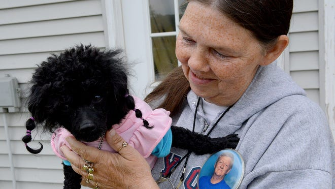 """Brenda Leonard holds Tinker Bell, one of her three poodles, as she talks about living in her """"campy,"""" a homemade trailer, Thursday, May 21, 2015. Hanging from her sweatshirt is a pin with a photo of her late husband, Doyle, who died in 2011 from pancreatic cancer. Brenda has memontoes of him strewn around her """"campy,"""" including shirts, pillows and other items with his photo on them. They were married 42 years when he died."""