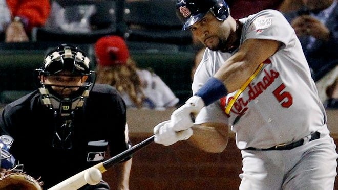 """FILE - In this Oct. 22, 2011, file photo, St. Louis Cardinals' Albert Pujols hits a solo home run during the ninth inning of Game 3 of baseball's World Series against the Texas Rangers, in Arlington, Texas. Pujols was drafted in the 13th round in 1999. He was in the majors by 2001, when he won Rookie of the Year honors and drove in 130 runs. Three MVP awards later, Pujols is closing in on the end of his career â€"""" with 656 home runs and counting."""