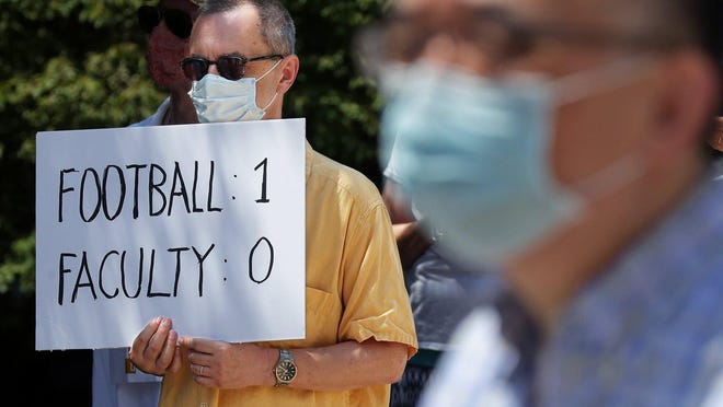A masked member of the University of Akron faculty holds a sign during a protest ahead of the faculty union's negotiations with the administration over budget cuts Thursday, July 2, 2020, in Akron, Ohio.